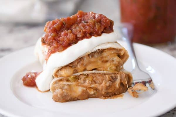 Freezer beef and bean burrito cut in half covered in salsa and sour cream.