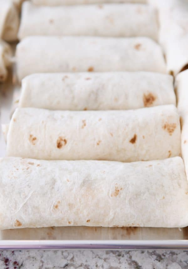Rolled freezer burritos on sheet pan.