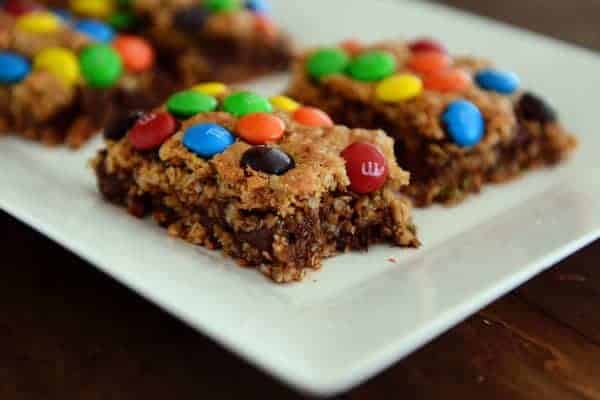 Cut up M&M topped chocolate oat bars on a white platter