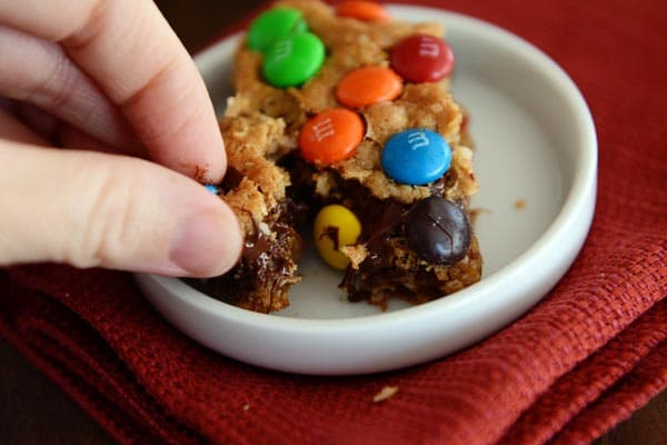 A hand taking a chunk off of an M&M topped oat bar in a small white ramekin.