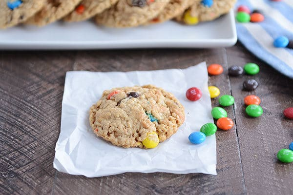 An M&M cookie on a piece of parchment paper with M&M's sprinkled on the side.