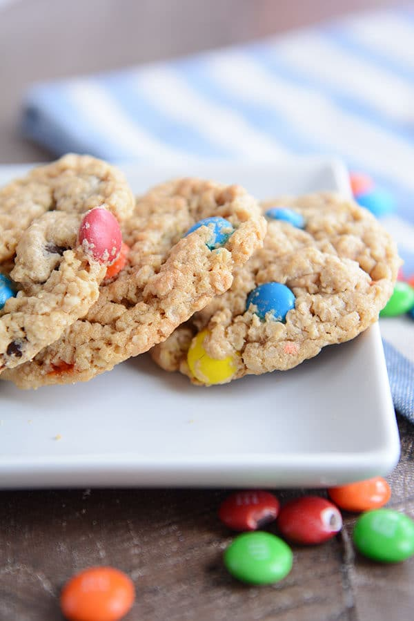 A white tray with three oat M&M cookies and a few M&M's sprinkled around the side.