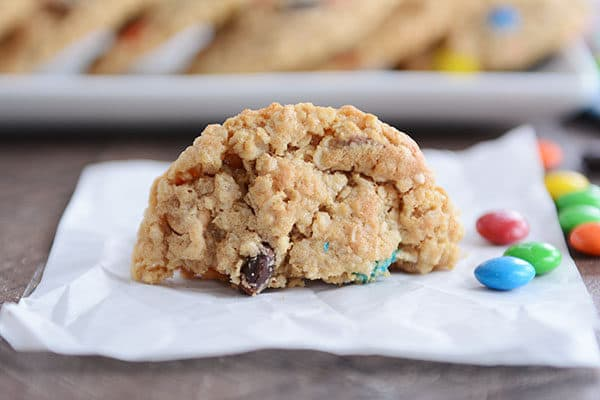 A half of an M&M cookie on a piece of parchment with a few sprinkled M&M's on the side.