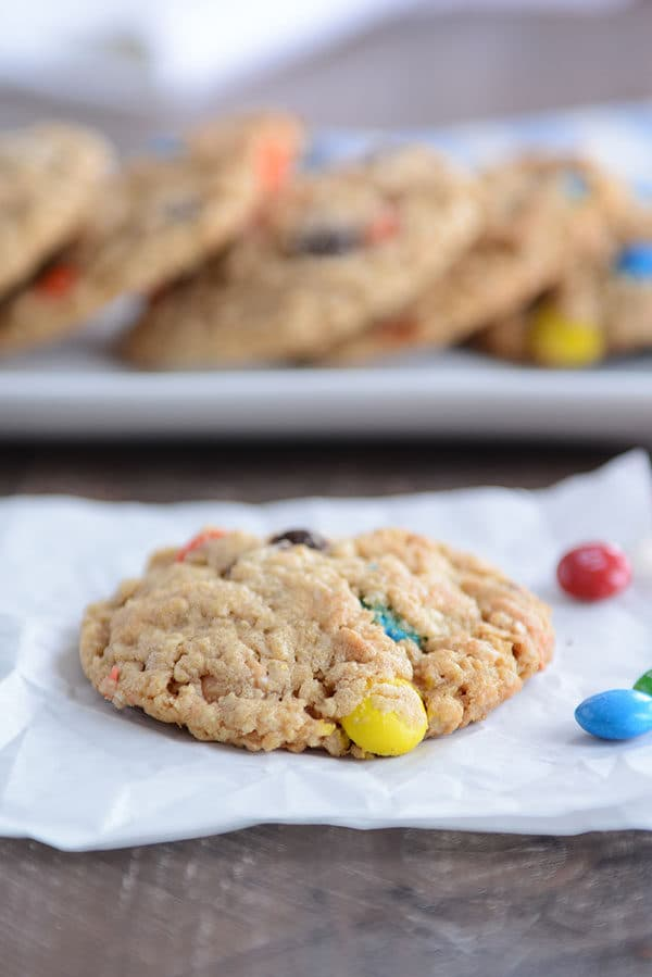 An M&M oat cookie on a piece of parchment with a tray of more cookies behind it.