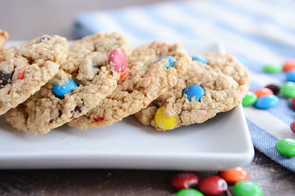 A tray of M&M oat cookies with additional M&M's sprinkled around the platter.
