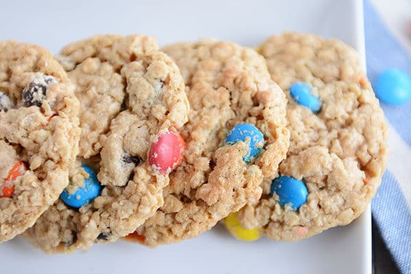 Four M&M oat cookies lined up side-by-side on a white platter.