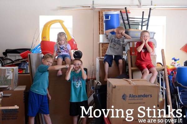Five little kids making silly faces surrounded by moving boxes.