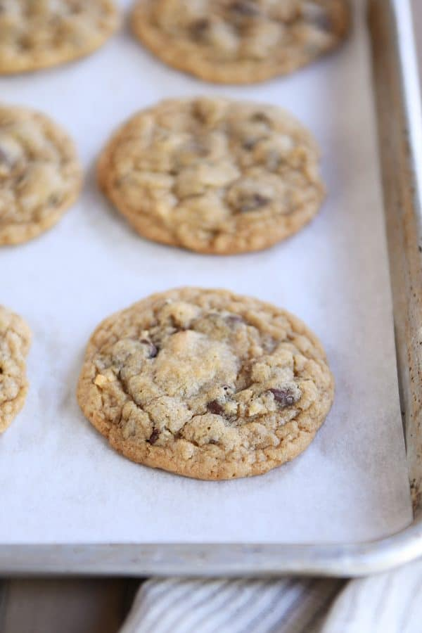 Soft and chewy oatmeal chocolate chip coconut cookies on sheet pan with parchment paper.