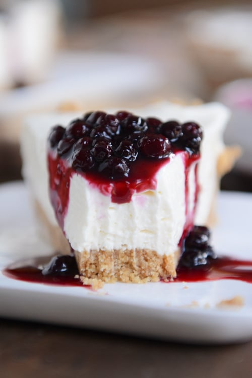 A slice of graham cracker crust no-bake cheesecake, with one bite taken out and blueberry sauce on top.