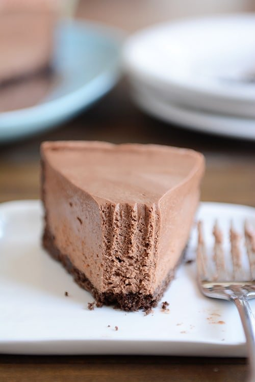A slice of chocolate cheesecake with chocolate crust with one bite taken out, on a white plate.