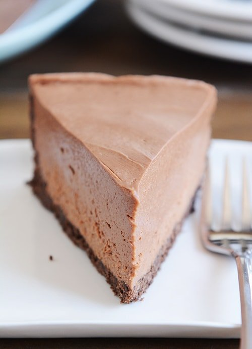 A slice of chocolate cheesecake with chocolate crust on a white plate.