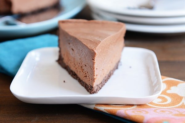 A slice of chocolate cheesecake with a chocolate crust on a white plate.