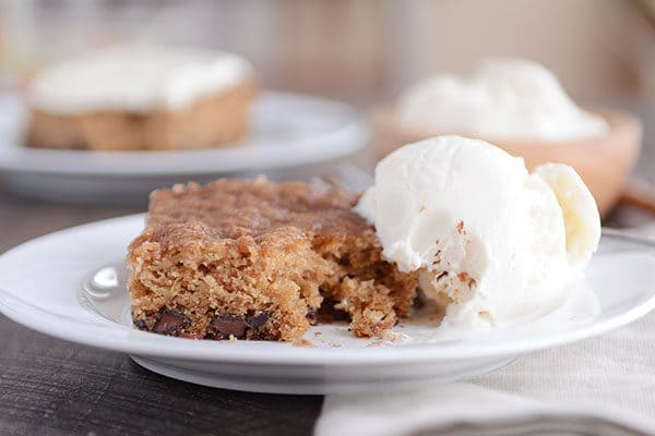A piece of oatmeal chocolate chip cake next to a scoop of vanilla ice cream.