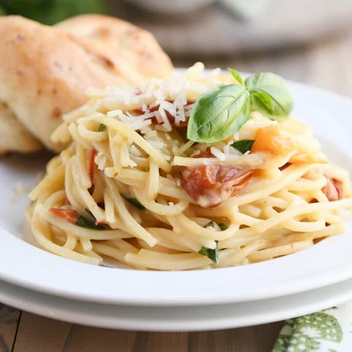 One pot creamy tomato basil pasta on white plate with parmesan breadstick.