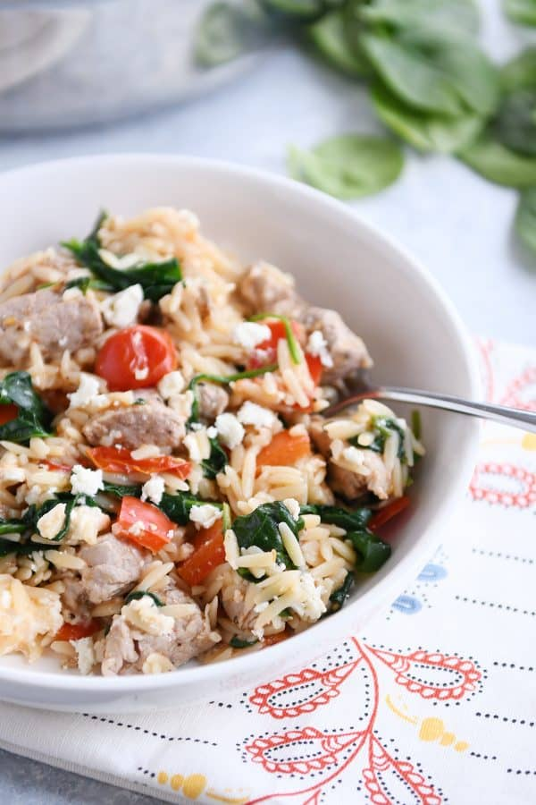 White bowl filled with orzo, spinach, bell peppers and pork.