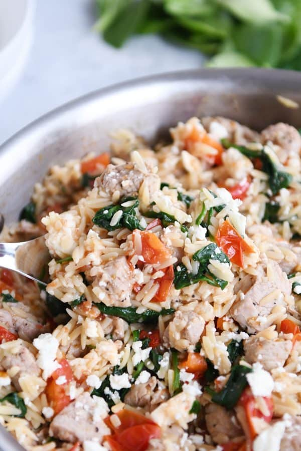 Mediterranean orzo skillet with serving spoon.