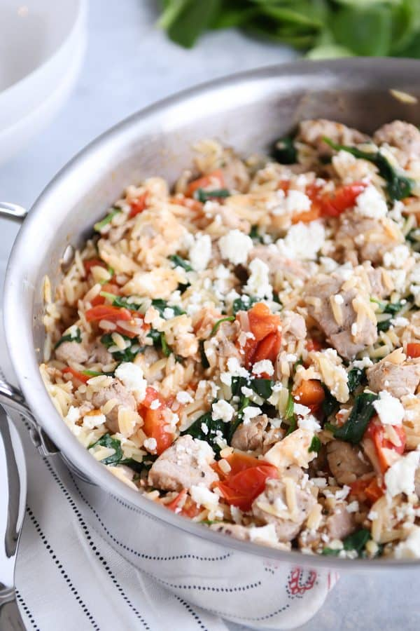 Stainless pan filled with Mediterranean orzo skillet with pork.