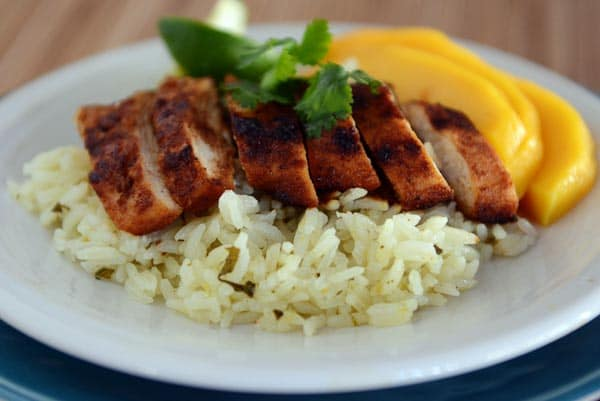 Slices of grilled chicken and sliced mango over a bed of rice.