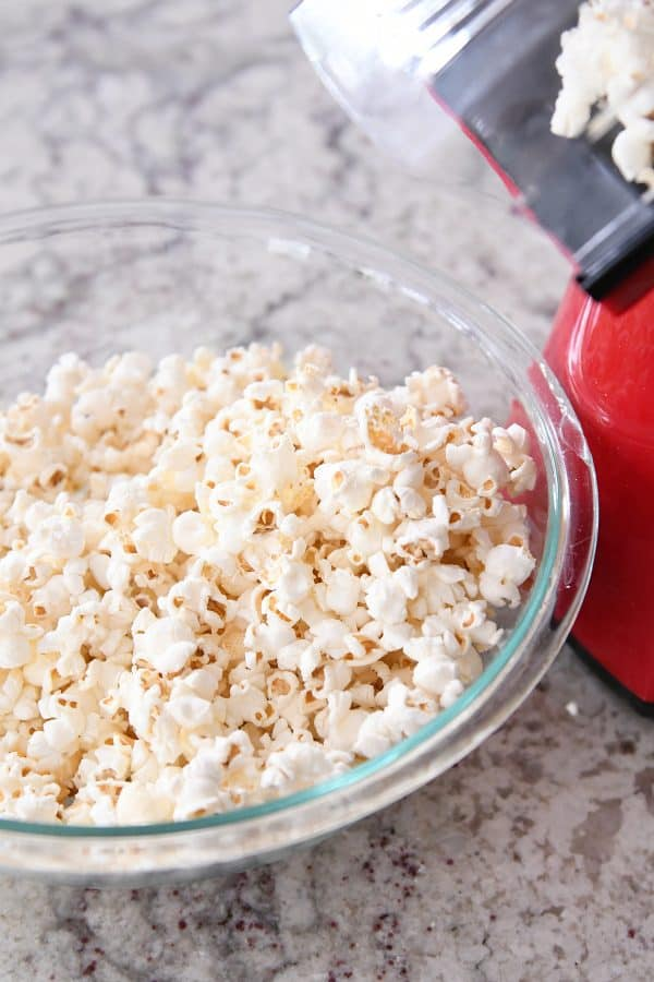 Air popper popping popcorn into glass bowl.