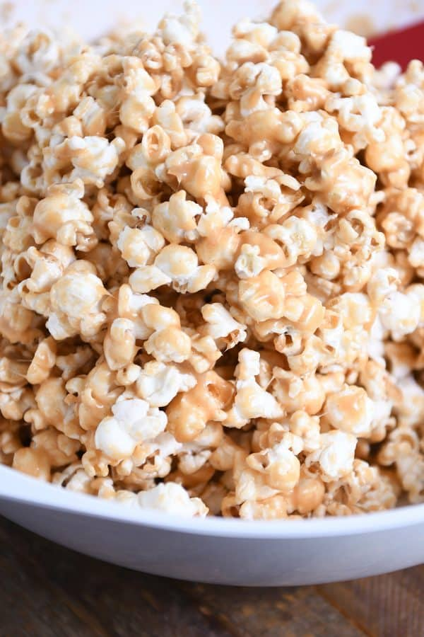 White bowl filled with soft and chewy peanut butter caramel popcorn.