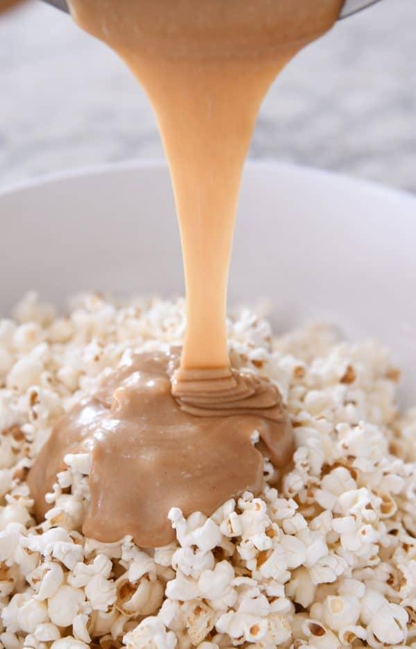 Pouring peanut butter caramel mixture over popcorn.