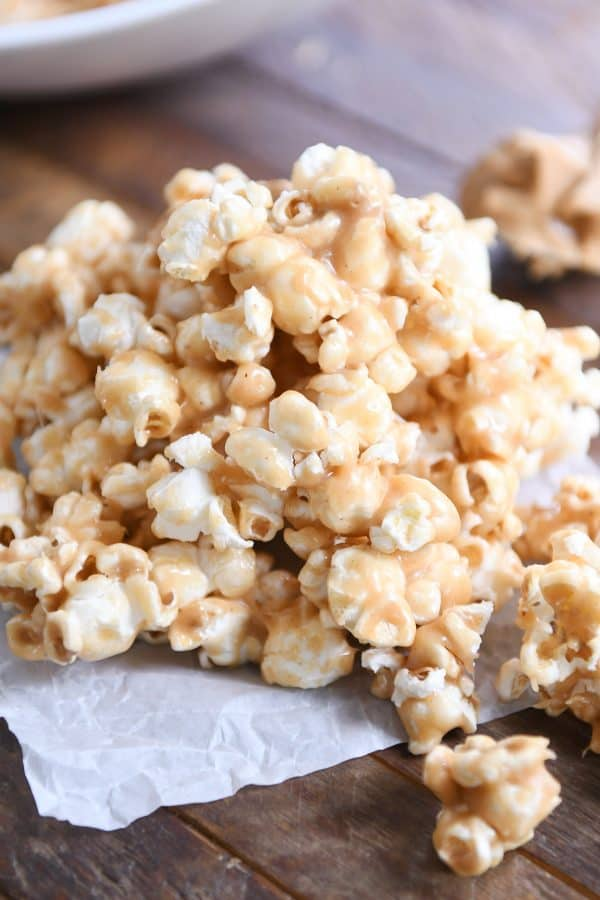 Pile of soft and chewy peanut butter caramel popcorn on was paper.