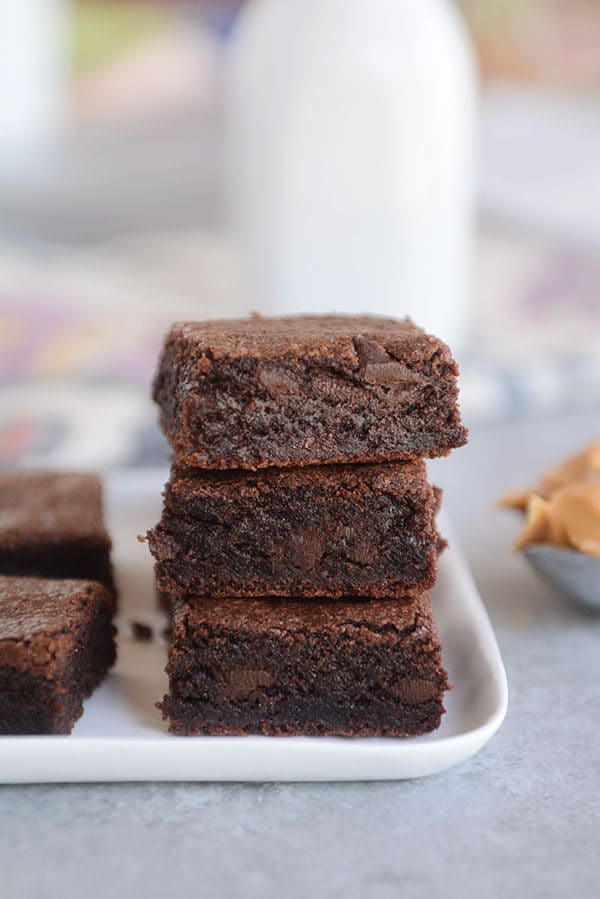 Three chocolate brownies stacked on top of each other on a white plate.