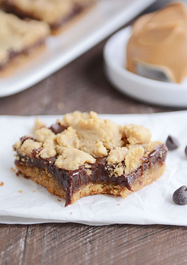 A peanut butter fudge bar with a bite taken out on a piece of parchment.