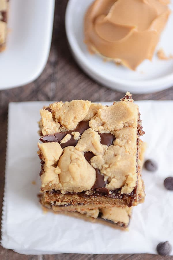Top view of a peanut butter fudge bar stacked on top of other bars on a piece of parchment.