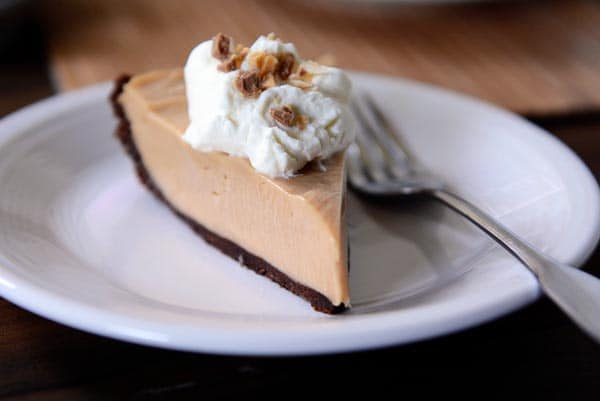 slice of chocolate crust peanut butter pie with whipped cream on a white plate