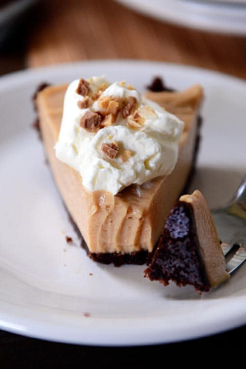 slice of whipped cream topped peanut butter pie with a chocolate cookie crust on a white plate with a fork taking a bite out