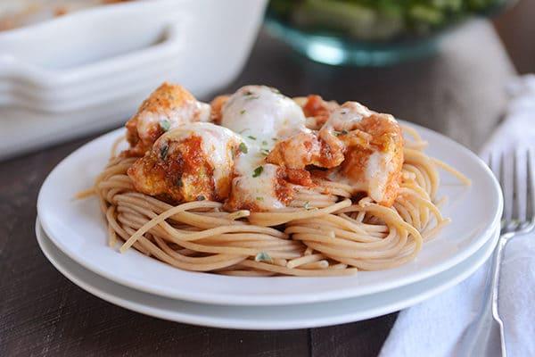 A plate of spaghetti topped with pesto marinara cheesy chicken.