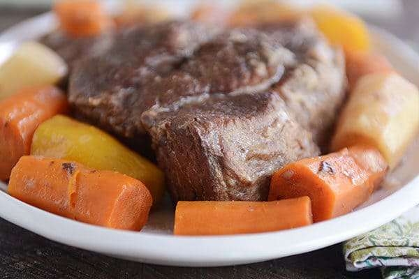 A white plate with a cooked beef roast in the middle and cooked carrots and potatoes all around it.