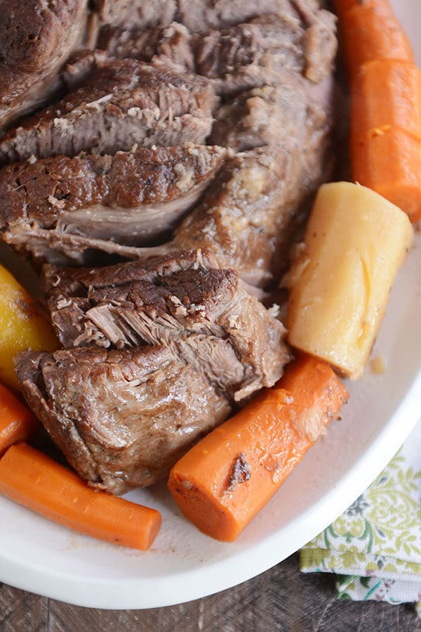 Top view of a pot roast sliced up with cooked carrots and potatoes around it.