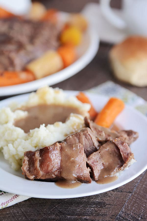 A plate of pot roast with gravy, mashed potatoes, and carrots.