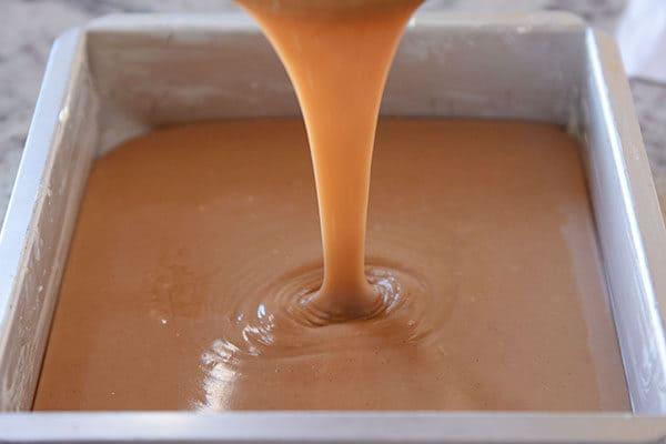 Liquid caramel getting poured into a metal tin.