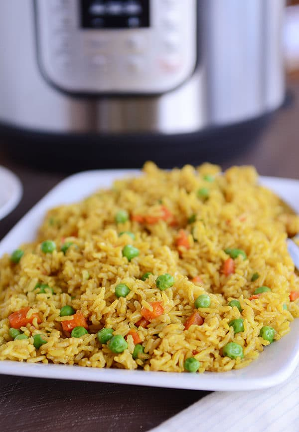 A white plate full of rice with peas and carrots sprinkled throughout, and an Instant Pot in the background.