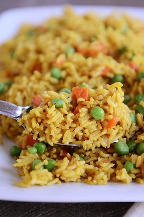 A spoon with a big scoop of yellow-tinted rice and peas and carrots sprinkled throughout.