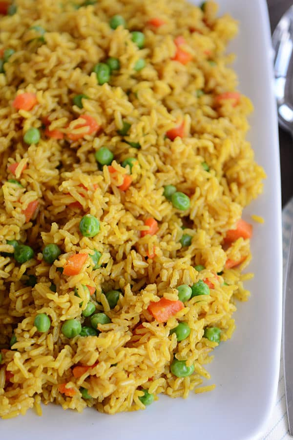A white platter full of yellow-tinted rice with peas and carrots throughout.