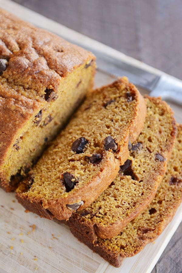 Three slices of pumpkin bread cut off the loaf of pumpkin chocolate chip bread.