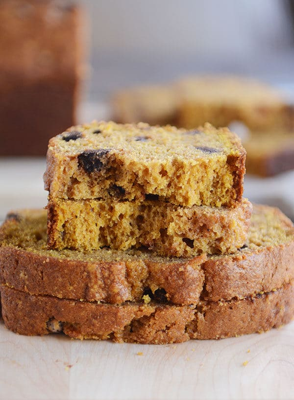 Three slices of pumpkin chocolate chip bread stacked on each other with the top slice split in half.