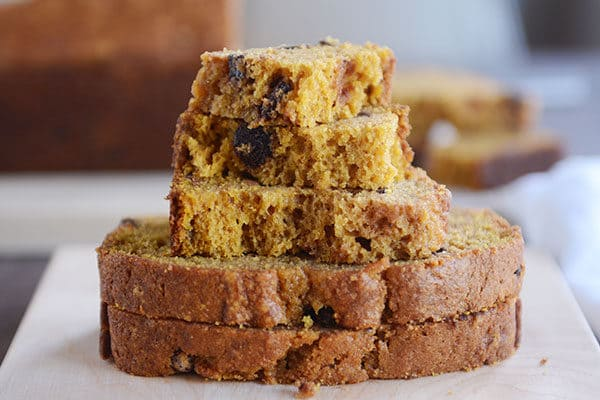 Thick slices and pieces of pumpkin chocolate chip bread stacked on top of each other.