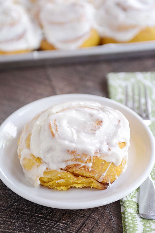 A frosted pumpkin cinnamon roll on a white plate.