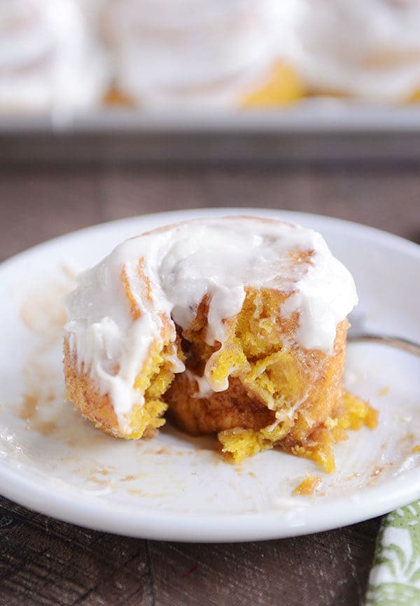 The center of a frosted pumpkin cinnamon roll with a bite taken out on a white plate.