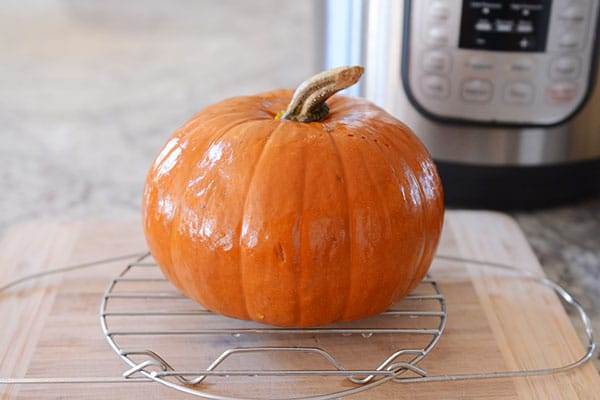 A small cooked pumpkin on a cooling rack.