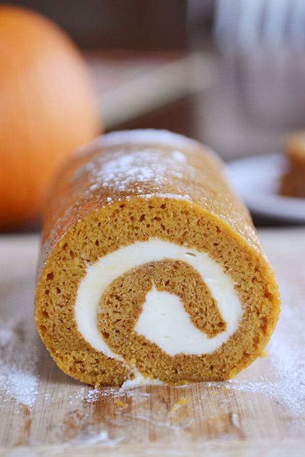 A front view of a pumpkin roll with a cream cheese swirl in it on a cutting board.