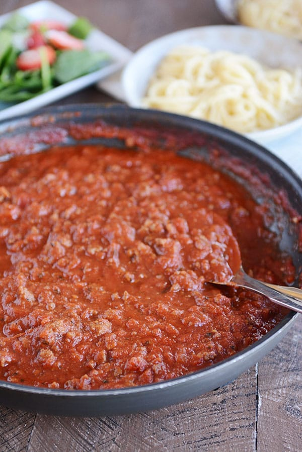 A skillet full of meaty, red spaghetti sauce, with a green salad, and spaghetti noodles in the background.