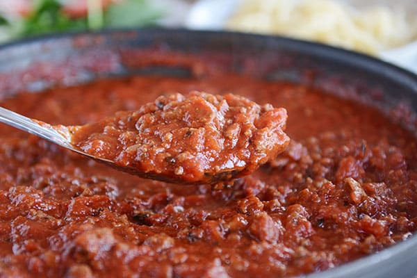 A spoonful of meaty, red spaghetti sauce over a skillet full of sauce.