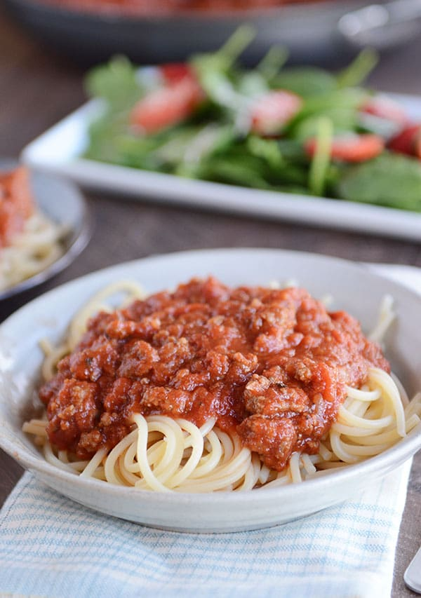 A white bowl of spaghetti noodles with meaty, red spaghetti sauce on top, and a green salad in the background.