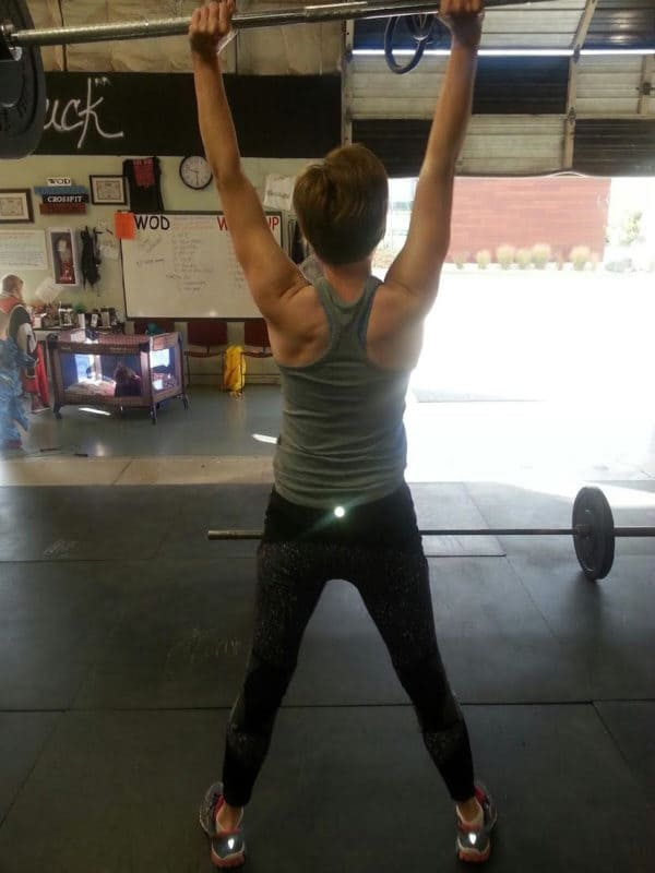 A lady lifting a barbell of weights over her head.